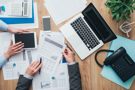 Business team working at office desk and analyzing financial reports, finance and accounting concept, top view