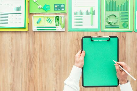 green environment: Businessman holding a clipboard with a blank green sheet and green office accessories on top, green business and environment concept
