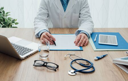 Professional doctor in his office working at desk, healthcare and hospitals concept