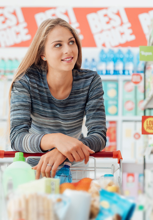 aisles: Young smiling woman at the supermarket, she is shopping and pushing a cart along the store aisles