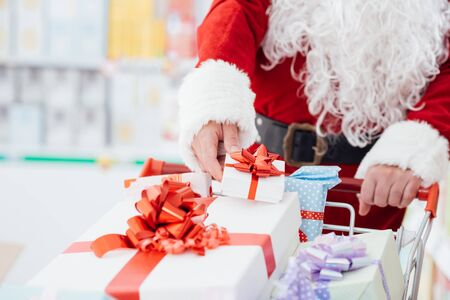 holiday spending: Santa Claus doing Christmas shopping at the supermarket, he is putting gift boxes in a full cart, holidays and celebration concept