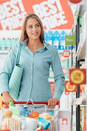 aisles: Young smiling woman pushing a shopping cart along the supermarket aisles and searching products on the shelves