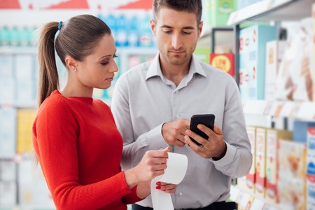 Couple doing grocery shopping at the supermarket they are checking a long receipt and using apps on the phone Stock Photo