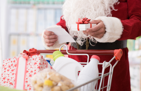 Santa Claus doing grocery shopping at the supermarket, he is pushing a full cart and checking a list, Christmas and shopping concept Stock Photo - 67277889