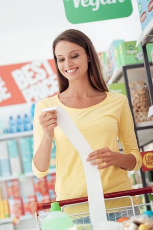 Young smiling woman shopping at the supermarket and checking a long grocery receipt Stock Photo