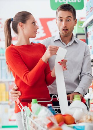 budgeting: Young couple shopping at the supermarket, they are pushing a cart and checking a long receipt, lifestyle and budgeting concept Stock Photo