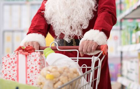 christmas spending: Santa Claus doing grocery shopping at the supermarket, he is pushing a full cart, hands detail, Christmas and shopping concept