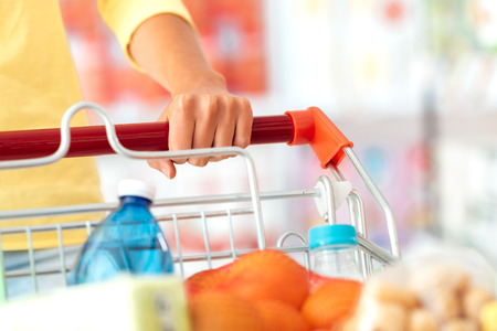 lifestyle shopping: Woman doing grocery shopping at the supermarket and pushing a full shopping cart, hand detail close up, lifestyle concept Stock Photo
