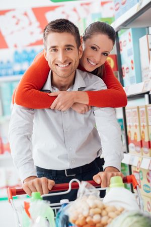 Cheerful loving couple doing grocery shopping together and pushing a cart along the store aisles