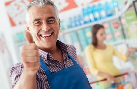 Happy supermarket clerk smiling and giving a thumbs up, he is smiling at camera Stock Photo