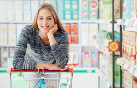Mujer sonriente joven que goza de compras en el supermercado, que se apoya en el carro lleno con la mano en la barbilla