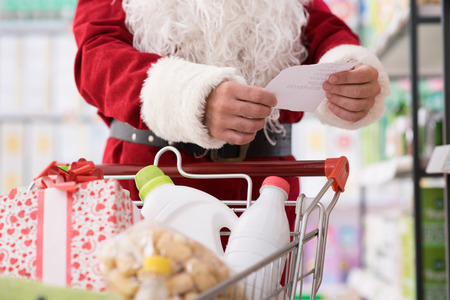 christmas spending: Santa Claus doing grocery shopping at the supermarket, he is pushing a full cart and checking a list, Christmas and shopping concept