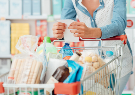슈퍼마켓에서 쇼핑하는 식료품을하는 여자, 그녀는 카트를 밀고 목록 확인