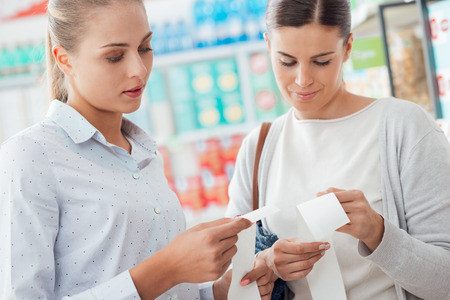 budgeting: Women shopping at the supermarket and comparing their grocery receipts, budgeting and lifestyle concept
