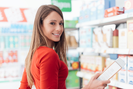 Woman doing grocery shopping at the discount store, she is holding a box and smiling at camera Stok Fotoğraf - 67177890