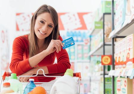 Lachende vrouw doen boodschappen bij de supermarkt ze leunt op een volle kar en met een creditcard