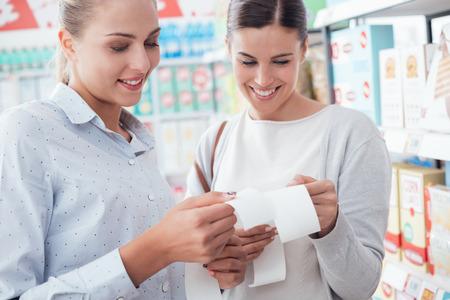 Mulheres que fazem compras de supermercado no supermercado e comparando o seu conceito recibos, estilo de vida e dinheiro