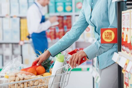 spending full: Woman doing grocery shopping at the supermarket, she is pushing a cart filled with groceries Stock Photo