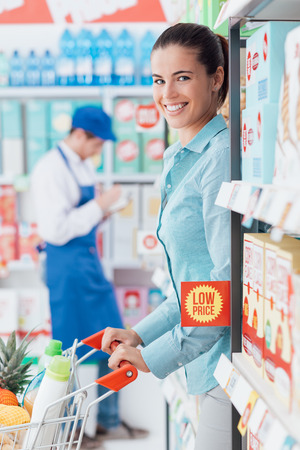 Happy young woman doing grocery shopping at the store, she is pushing the cart along the store aisles Stock Photo