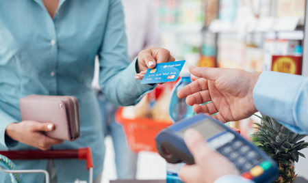 Kobieta przy kasie w supermarkecie, jest ona płacenia za pomocą karty kredytowej, zakupów i koncepcja sprzedaży detalicznej