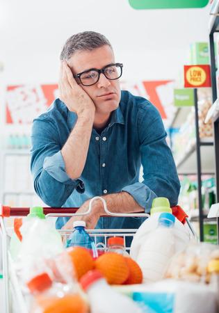 Triste hombre agotado de compras en el supermercado, él está apoyado en el carrito de compras completo