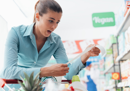 gasping: Woman checking the grocery receipt at the supermarket, she is shocked and gasping because the bill is very expensive