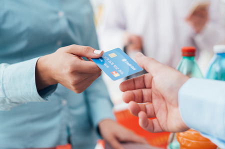 Woman at the supermarket checkout, she is giving her credit card to the cashier, retail and payments concept