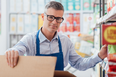 Professional supermarket clerk working in the store aisle, he is sorting items on the shelf