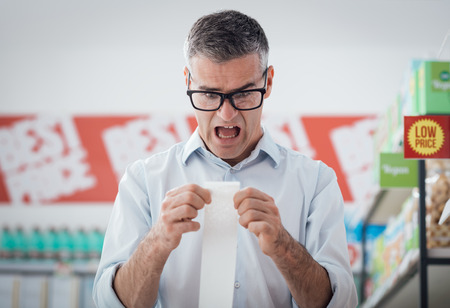 Shocked man doing grocery shopping at the supermarket and checking a long receipt, lifestyle and budgeting concept