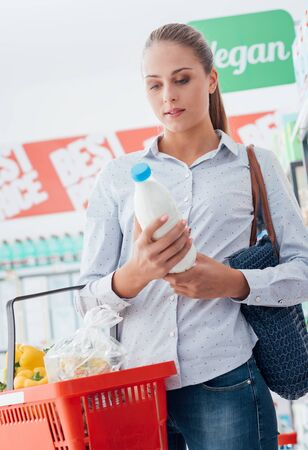 checking ingredients: Woman shopping at the supermarket and reading a food label on a milk bottle