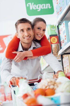 aisles: Cheerful loving couple doing grocery shopping together and pushing a cart along the store aisles