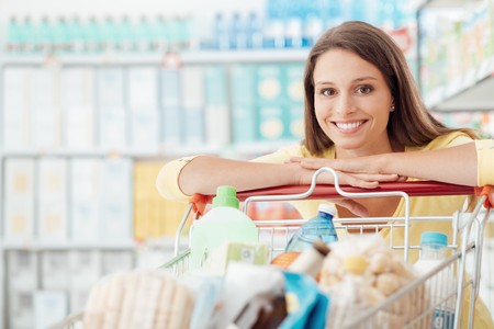 Smiling happy woman enjoying shopping at the supermarket, she is leaning on a full cart, lifestyle and retail concept