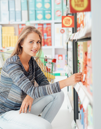 market bottom: Beautiful woman doing grocery shopping at the supermarket, she is taking products on the store shelf
