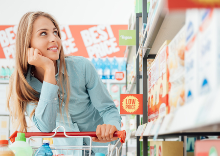 Attractive happy woman at the supermarket, she is doing grocery shopping and leaning on the cart