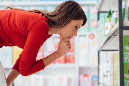 Young woman choosing products on the supermarket shelves and reading labels, she is thinking with hand on chin Foto de archivo