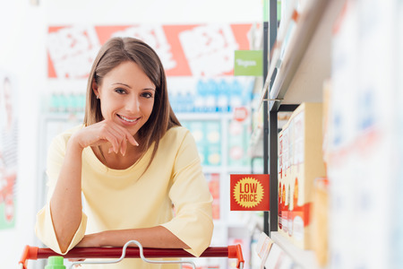 lifestyle shopping: Happy woman doing grocery shopping at the supermarket, she is leaning on a full shopping cart, lifestyle and retail concept