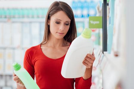 Vrouw die bij de supermarkt winkelt en detergentproducten vergelijkt, leest zij etiketten