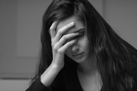 woeful: Sad depressed woman touching her forehead and looking down, stress and exhaustion concept