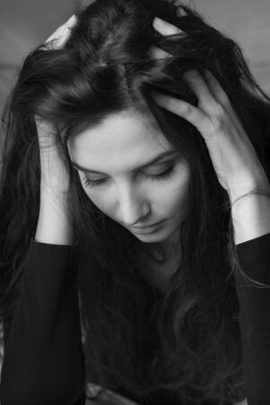 woeful: Desperate woman with head in hands, she is having an headache, depression and sadness concept
