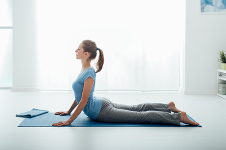 Woman practicing yoga and meditation at home on the floor, she is doing the cobra pose