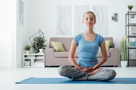 Jeune femme à la maison à pratiquer le yoga sur le sol, style de vie sain et le concept de remise en forme