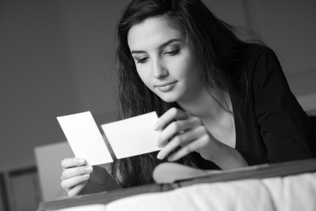 photo pictures: Young woman relaxing on the bed at home, she is watching old pictures on a photo album and lying down Stock Photo