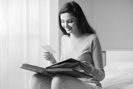 photo pictures: Young serene woman sitting on the bed at home and watching old pictures on a photo album