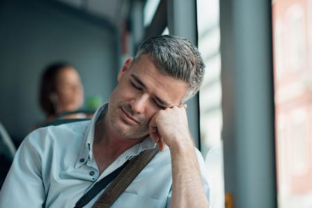 gente durmiendo: hombre cansado que se sienta en el autobús y el sueño, que se apoya en el brazo