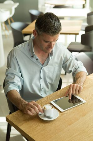 people   lifestyle: Man having breakfast at the cafe, he is drinking an espresso and connecting with a touch screen tablet