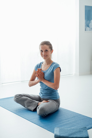Woman practicing yoga and meditation at home on the floor, she is sitting with hands clasped