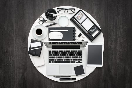 business equipment: Business and office desktop equipment in a white circle on a dark elegant desk, flat lay