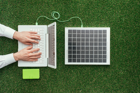 electrical energy: Man working with a laptop on the grass connected to a solar panel, alternative energy sources and electrical power generation concept Stock Photo