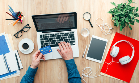 Man working at desk and purchasing products online, he is making a payment using a credit card, online shopping concept
