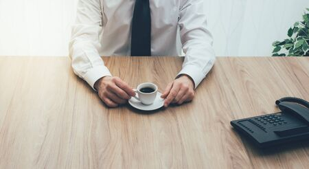 unrecognizable person: Corporate businessman sitting at office desk and having a coffee, unrecognizable person Stock Photo
